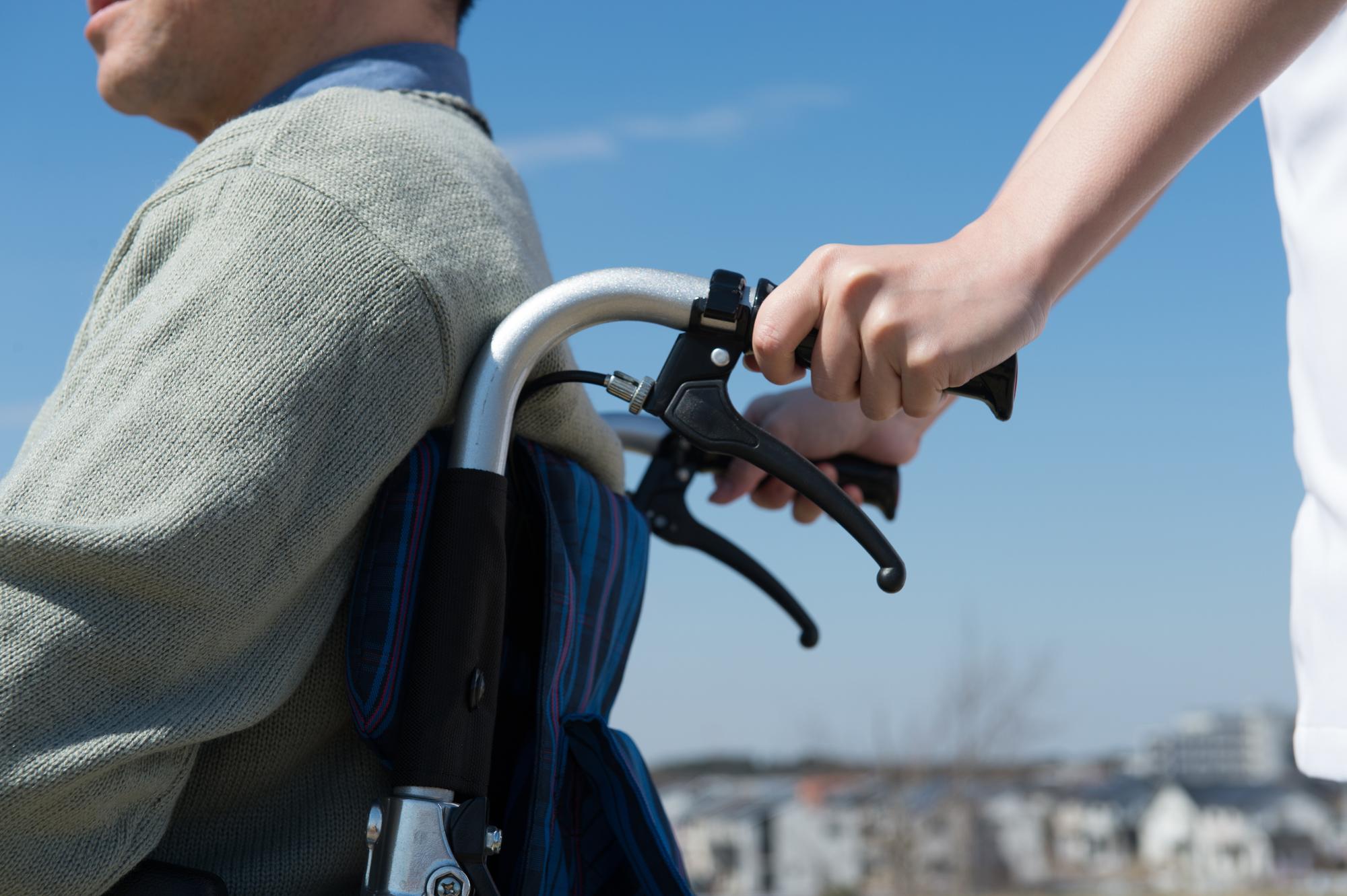 シニアの車椅子を押すヘルパー